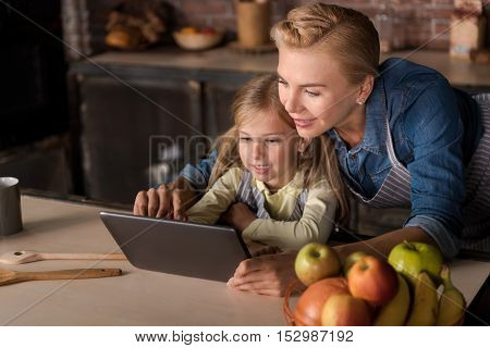 We resting. Amused happy little girl looking at the tablet with her mother while sitting at the table and having fun in the kitchen