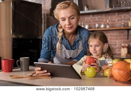 We looking for the best recipe. Delighted involved little girl holding apples and sitting at the table with her mother while looking at the tablet and expressing joy in the kitchen