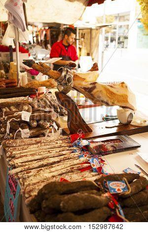 FIGUERES, SPAIN - OCTOBER 12, 2016: Jamon Serrano for sale at Figueres. The vendor is slicing Spanish Jamon Iberico (serrano ham)