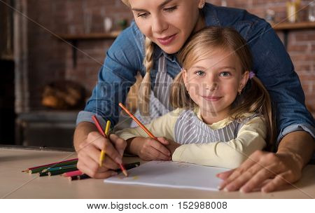 Enjoyable time. Smiling cheerful happy girl drawing with her mother while sitting at the table and expressing joy at home
