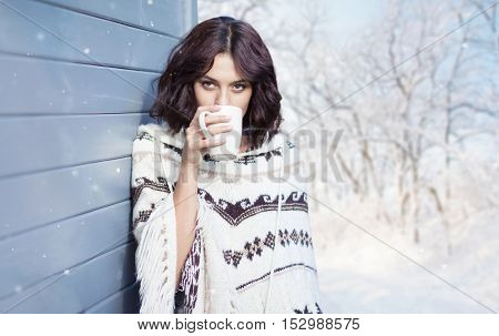 Beautiful natural young brunette woman with cup of coffee, wearing knitted poncho, standing outdoor at the house. Winter snow woods landscape in the background