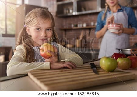 I adore apples. Cheerful happy smiling girl holding apples and sitting at the table in the kitchen while her mother cooking in the background