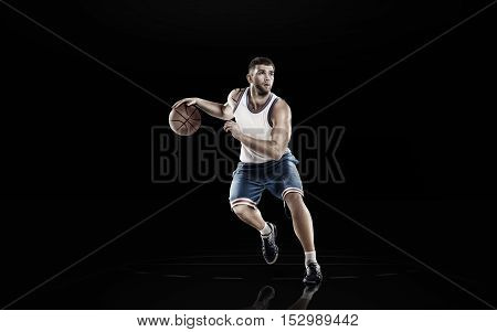 Young basketball player in action isolated on black background
