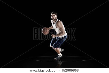 Professional basketball player in action with ball isolated on black background