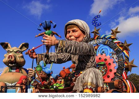 Putignano,Apulia,Italy - February 15, 2015: carnival floats, giant paper mache. European politician: Angela Merkel. Carnival Putignano: floats. Angela Merkel torture the European Community.Carnival Putignano: floats.  Angela Merkel torture the European Co