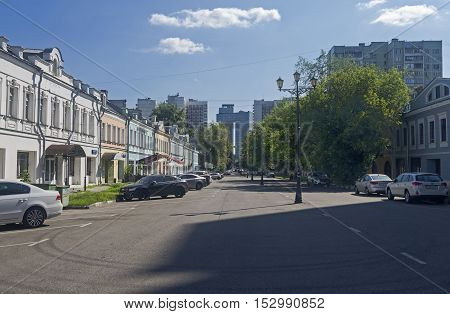 MOSCOW RUSSIA JULY 31 2016: The contrast between the old and the modern urban buildings. Shkolnaya street Moscow Russia. Quiet July morning.