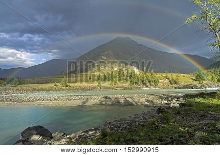 Rainbow over the river. Argut River merger with Katun. Altai Mountains Russia. August.