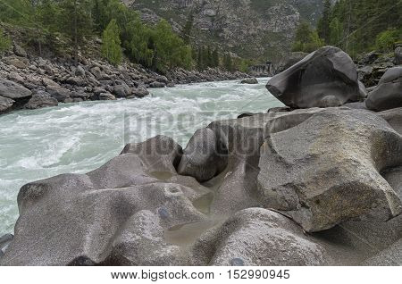 Bizarre stone on the shore of a mountain river. Rapids
