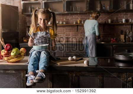 Merry weekend. Cheerful merry smiling girl holding the bowl and mixing eggs while sitting on the table in the kitchen and her mother cooking in the background