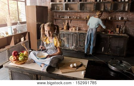 In a good mood. Pleasant delighted smiling daughter holding the bowl and mixing eggs while sitting on the table in the kitchen and her mother cooking in the background
