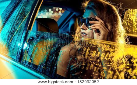 Fashionable blonde beauty in a car, at the evening