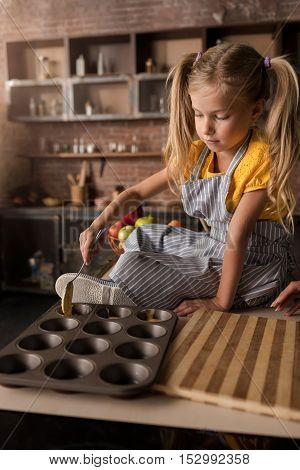 Involved in the process. Concentrated involved little girl putting the pastry in baking rings while sitting on the table in the kitchen and cooking
