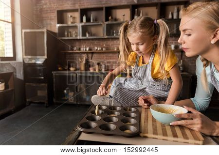Involved in the cooking. Concentrated involved little girl putting the pastry in baking rings with her mother while sitting on the table in the kitchen and cooking