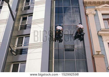 Two Workers cleaning windows service on high rise building