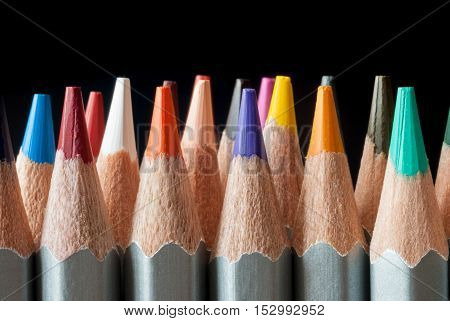 Set of colored pencils on a black background. Sharpened colored pencils. Ready to paint.
