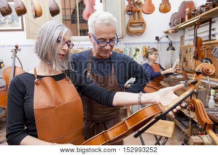 Group Of Mature Violin Maker In Pose