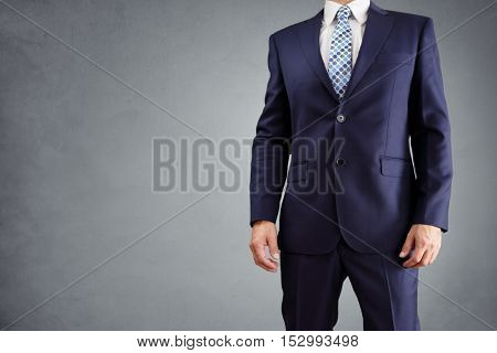 Businessman in a blue business suit isolated on gray background with copy space