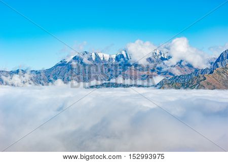 Mountain top above the clouds at autumn evening time. Caucasus. Russia.