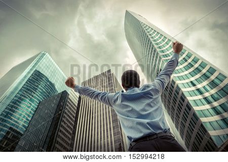 Businessman. Happiness businessman around skyscrapers in La Defence district in Paris City with sky background.