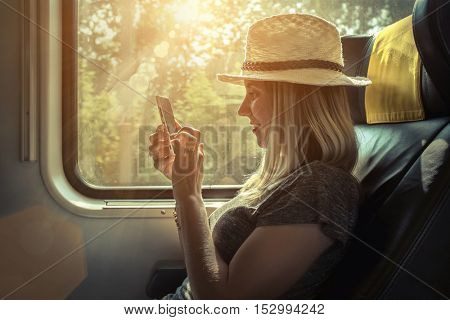 Woman sitting at train and looking to mobil phone under sunlight at day time.