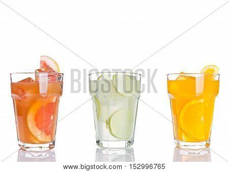 Glass of orange grapefruit and lemon juice iced on white background with reflection