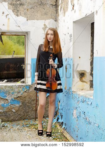 Beautiful woman with violininside old broken house