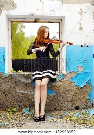 Beautiful girl playing violin inside old broken house