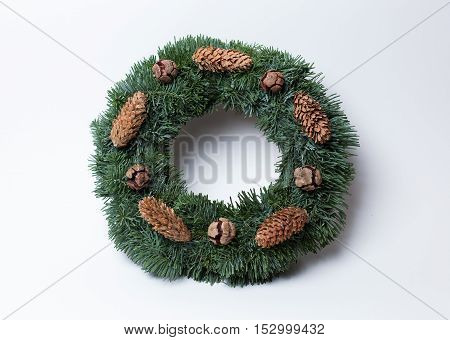 Christmas wreath of fir branches decorated with pine cones and cypress cones on white background