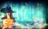 Halloween Witch with a magic Pumpkin in a dark forest. Beautiful young woman in witches hat and cost poster