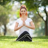 Yoga outdoor. Happy woman doing yoga exercises, meditate in the park. Yoga meditation in nature. Con poster