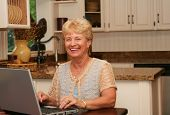 stock photo of nana  - Grandma using her laptop in the kitchen - JPG