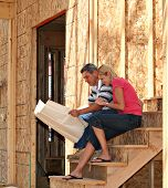 Young couple looking at the blue prints of their new home.