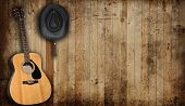 stock photo of headgear  - Cowboy hat and guitar against an old barn background - JPG