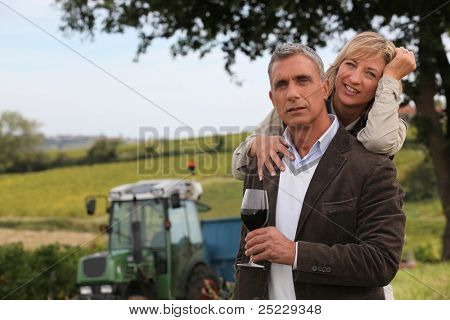 couple of wine producers in front of vines