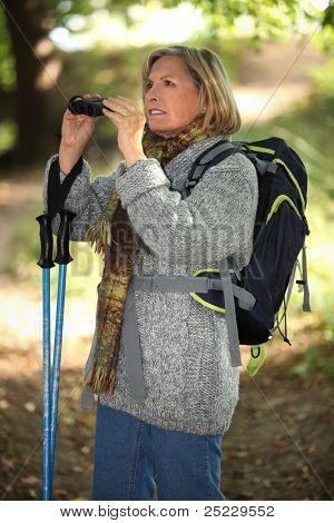 60 Jahre alte blonde Frau Landschaften mit Fernglas erwägt, trägt sie warme Kleidung ein