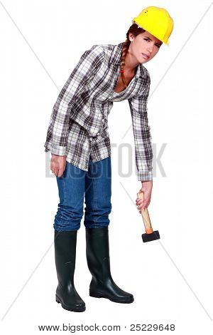 A tired female construction worker with a hammer.