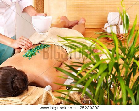 Young woman getting salt massage.