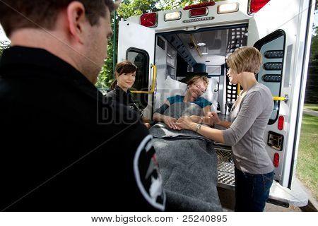 Paramedic team placing senior woman in ambulance, caregiver at side