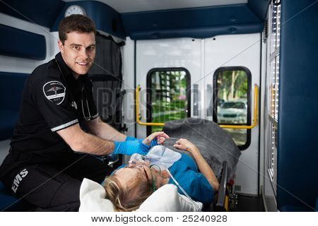 Portrait of a male EMT inside ambulance with senior woman patient