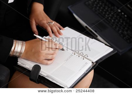 Businesswoman taking notes into personal organizer, closeup hand holding pen.?