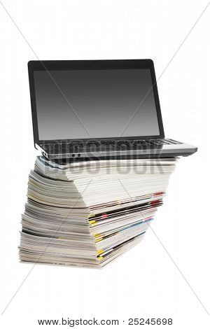 On-line magazines -Laptop on a pile of magazines