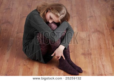 Sad or depressed woman sitting on the floor