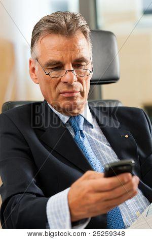 Jefe en su oficina de correos de comprobación y leyendo periódicos