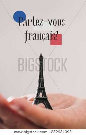 poster of a miniature of the Eiffel Tower on the hand of a young man and the question parlez-vous francaise, d