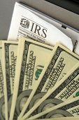 picture of irs  - Stack of hundred dollar bills laind out on top of IRS form paying taxes or getting a refund
