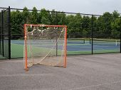 Offseason, Beat Up, Rusted, Ragged Lacrosse Goal Sitting On Asphalt Court, Nets Tearing poster