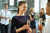 Smiling glamorous girl with champagne having talk to guy while enjoying home party poster