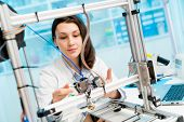 female student or laboratory assistant in the automation laboratory is debugging the work of the 3d  poster