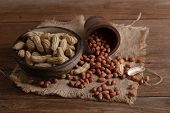 Peanuts In Nutshell On A Piece Of Wooden Bowl And Peeled Peanuts On Sackcloth poster