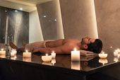 Young man relaxing on massage table surrounded by scented candles at Asian spa and wellness center poster